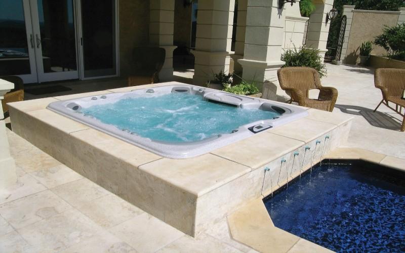Vířivka Sudnance Spas vedle bazénu zabudovaná v terase