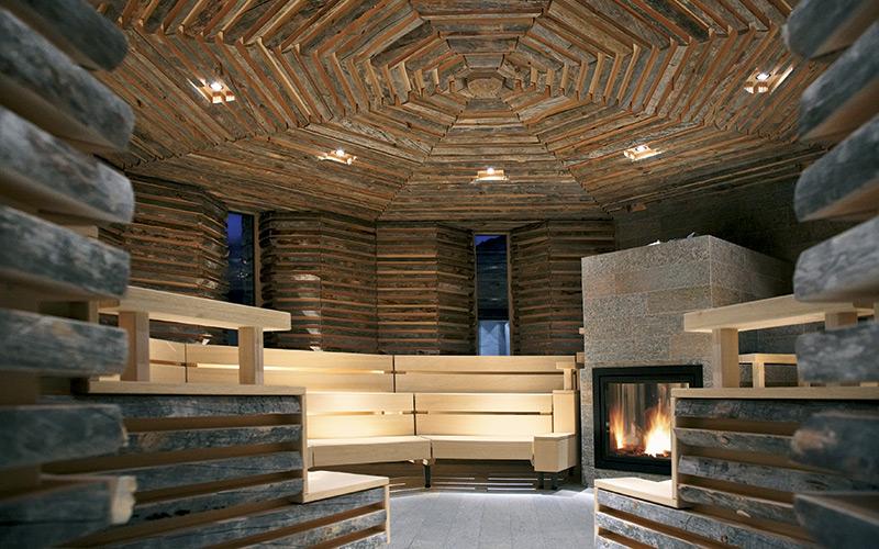 Moderní sauna Klafs umístěná v místnosti obložené neopracovaným dřevem