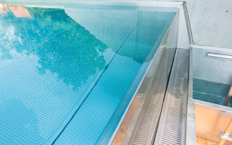 Přeliv nerezového bazénu s mřížkou umístěnou pod úrovní bazénu