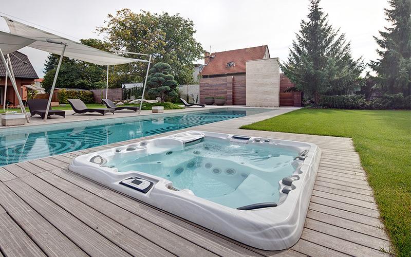 hydromasážní vana na zahradě vedle bazénu